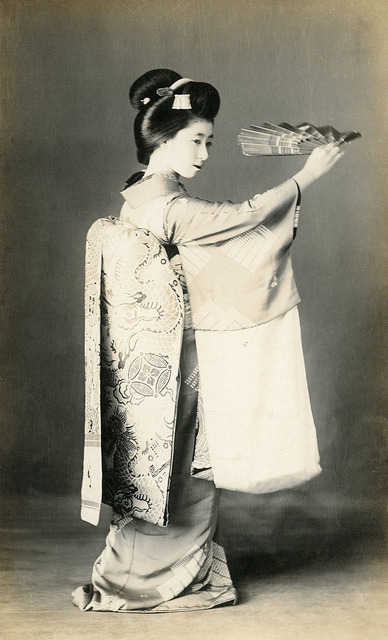 "Dragon and Pearl Obi 1910s by Blue Ruin1 on Flickr.  Via Flickr: Maiko (Apprentice Geisha) Momotaro, dancing with a mai-ogi (dancing fan), her obi (sash) decorated with dragons and pearls. ""The dragon is often depicted surrounded by little flames and running after a [spherical] jewel, tama, sometimes having caught it in its claws. This is the jewel of omnipotence, the jewel that fulfils all desires, often represented in Far Eastern art. Some authors are explaining this jewel as the sun hidden by rainclouds. Others… hold the opinion that it represents the thunder."" According to ""The Animal in Far Eastern Art"" by T. Volker, first published 1950, page 64."