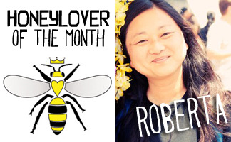 "HoneyLover of the Month: ROBERTA  ""Beekeeping started out just as way to improve my crops. Seemed easy enough to just get some free bees off a tree limb and stick them in a box and voila, more fruit. Well there was something about my first day that was just magical. I went to watch Kirk do a cutout with someone who had some experience. I came from work and they had gotten most of a very old and big hive out of wall. I got to just watch and learn. The next door neighbor and her kids were watching from a window and I loved being the person explaining what was happening. Kirk was mentoring, the other beekeeper was learning how to do a cutout, I was just learning how to be around bees and the kids were learning about something so new. Then Kirk took me to a simple swarm capture and we packaged them up into one of his old nucs and there I was with a new hive. With the swarm, it was just a small cute ball of fuzzy bees. They were gently, buzzing but pretty much content to go wherever we put them. Seemed like an innocent experience. The excitement of being able to work with these little but powerful creatures took a hold and I had bee fever. I couldn't get enough cutouts and swarms but then I couldn't keep them anywhere and that's how the mentoring started. I loved being able to share a first time cutout or swarm with others. It really felt like giving someone a gift."""