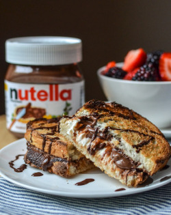 prettygirlfood:  Hot Baked Nutella & Cream Cheese Sandwich serves 4 8 slices soft yet crusty Italian bread4 ounces cream cheese, cut into 4 cubes and softened4 to 6 tablespoons NutellaFlaky saltMelted chocolate, to garnishFresh berries, to serve Heat the oven to 450°F. Line a baking sheet with parchment or a Silpat. When the oven is hot, lay each slice of bread on the baking sheet and put in the oven. Turn the oven to BROIL and toast the bread for 2 to 3 minutes or until golden brown. Remove from the oven. Spread a softened cube of cream cheese on the toasted side of four slices of bread, one cube to each. On the other slices, spread a thick layer of Nutella. Sprinkle each slice very lightly with salt. Put the sandwiches together and put back in the oven. Broil for 1 1/2 to 2 minutes on each side. Remove when both sides of the sandwich are toasted golden brown. Cut each sandwich in half and drizzle with melted chocolate. Place on plates and surround with fresh berries. Serve immediately.