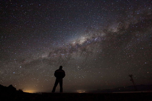 distant-traveller:  Admiring the heavens  It is difficult for even the most seasoned astronomer to resist taking time out of a busy observing schedule to stop and stare up at the gloriously rich southern sky. This image is a self portrait taken by astronomer Alan Fitzsimmons, who took this photo between observing sessions at ESO's La Silla Observatory. This bold photo shows the contrast between a simple, still and dark figure on Earth and the brilliant and bright starry night sky. In this picture, the sky is dominated by the enormous splash of stars and dust which make up the centre of the Milky Way, our home galaxy. ESO's observatories are located in the Atacama Desert in northern Chile, a region with very few inhabitants, which combines very dark nights with extremely clear atmospheric conditions, both factors conducive to making high quality observations.  Image credit: ESO/A. Fitzsimmons
