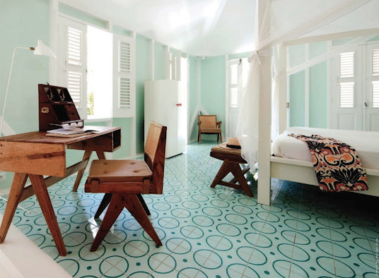 Pale aqua tiles create a bubbly circular pattern in this bedroom. Together, the coordinating walls, mosquito netting on the bed, and white shuttered windows create a modern beach vibe that will make you feel like you are on holiday every day.