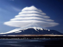 teenage-hoodlum:  Lenticular clouds over Mount Fuji, Japan. These are stationary lens-shaped clouds that form at high altitudes, usually perpendicular to the direction of the wind.