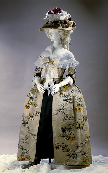 Gown from silk made by Anna Maria Garthwaite (1690-1763), 1740's England, altered 1780's (fabric made in Spitalfields, London), the Victoria & Albert Museum    Object Type Originally, the gown was probably a sack back, with loose box pleats at the back to allow for maximum display of the silk pattern. The gown would have been open down the front, with folded-back robings and rectangular cuffs at each elbow. The last conversion in the 1780s to the style of that time was quite clumsily executed, suggesting that perhaps the gown had been handed down to a maid. Design & Designing The design is brocaded in coloured silks on oyster-coloured satin. Two large sprays of flowers fill the width of the repeat, linked by upward and downward trails of bright pink berries and rose buds. Among the identifiable flowers are roses, morning glory and auricula. From both sprays the flowers on upward stems are brocaded in shades of pink, fawn, lilac, white and black, while those hanging down are in shades of blue, yellow and red. A variety of greens colour the stems and leaves, and the flowers are shaded naturalistically by the weaving technique. People The freelance textile designer Anna Maria Garthwaite (1690-1763) received at least 40 commissions for silk designs from a Spitalfields master weaver called Mr Gregory. The design for this silk was one of them. There were a number of members of the Weavers' Company with the name Gregory, so we do not know his exact identity, but the designs she produced for him are some of Garthwaite's prettiest and most fashionable, and include patterns for brocaded lustrings, damasks, tissues and satins.
