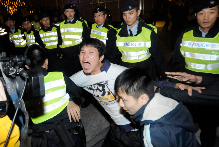 HONG KONG (01/01/13) — A protestor is escorted by police during a protest against the city's leader Leung Chung-ying in Hong Kong on January 1, 2013. Tens of thousands of protesters took to the streets of Hong Kong on January 1, calling for the city's embattled leader to quit and demanding greater democracy 15 years after it returned to Chinese rule. Photo by Justin Chin