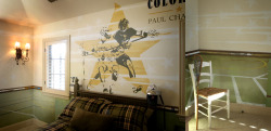 Boy's room dilemmas? - never fear, Michelle is here. This lacrosse mural has to be one of my favorite rooms I've ever painted. Mom knew she wanted some sort of retro looking lacrosse art reproduced above the bed but, beyond that, I was free to play. This room is big and I imagined that a simple image above the bed wouldn't be 'enough'. The room was asking for more. We played with an poster image we found, changed the colors (to match the bedding) and added a player to make the design a bit more horizontal. The lower walls are painted green, given a faux treatment to mimic grass and then I painted on 'turf' lines. The result is a collage of segments of lacrosse fields. The final touch with the paint is a bit of tone on tone white detail here and there on the upper walls. But the creme de la creme is chair rail made out of actual lacrosse sticks mounted to stained molding.