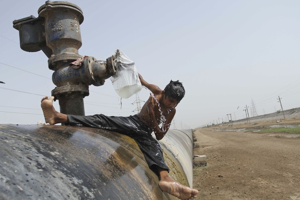 A boy bathed under a leaking water pipe on a highway in the Gujarat state, India, Wednesday. Ajit Solanki/Associated Press