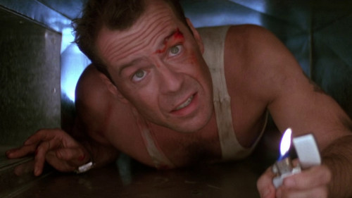 A few thoughts on Die Hard (1988) • Cigarettes: I hadn't seen the original Die Hard for years until I rewatched it again last night with my wife, who'd somehow never seen it, and a few friends. One of the first things that struck me, having not really watched any older action film in a while is John McClane is one smoke-happy action hero, pulling out a cigarette the moment he gets off a plane and smoking every chance he gets until the end. Typical of the film, which doesn't let any element go to waste, his habit plays into the plot, allowing him to learn a bit about the bad guys based on the brand they smoke, and providing another way for the film to show the passing of time based on the number of smokes left in his pack. Bruce Willis smokes beautifully, too, letting his attitude toward the butt in his hand express his mood. It all plays into the film as a whole without drawing too much attention to itself. There's a reason this movie got ripped off so much in subsequent years: It's a model of how to make a tense thriller without losing sight of the characters, or why we should care about them. • McTiernan: That efficiency's there in the direction, too. There are a number of John McTiernan films I haven't seen, including The Hunt For Red October, which people seem to like. But I don't think too many object to the statement that this is finest hour. (Predator never impressed me that much, but I guess an argument could be made for it.) I've seen enough of his later films to know he lost the flair on evidence here, becoming just another competent-enough action hand who directs like he's seen Die Hard a few times. What happened? Was it having Jan DeBont as his DP that made the difference? If nothing else, DeBont captures some the most apocalyptic-looking L.A. sunset I've ever seen. • California: One trick the film pulls off with the same sort of efficiency is the way it slowly adds to its cast, bringing in cops, reporters, and FBI agents until it becomes a real Los Angeles movie. That all the action—and most of the movie—takes place in a single skyscraper helped make Die Hard stand out in 1988 but the way that location becomes the focus of the entire city over the course of the film makes the canvas feel much broader. So does MacClane's New York-born distaste for casual California culture. It's little more than a collection of eye roll-inducing California clichés floating through the '80s (though, oddly, no sushi jokes), but Willis makes it work. • Women: The background business of the movie is MacLane's attempt to repair his marriage and I'd never noticed before how the first act of the film keeps throwing attractive women in his path only to have him notice them and pass them by. He's got other business, not that the thought doesn't cross his mind. (Even once the action starts, there's still that nudie calendar posted in the back passageways that he uses to mark his place. • The towering inferno: It's not as easy to watch Nakatomi Plaza explode the as it was before 9/11. All those falling bodies and office paper floating against ash and smoke doesn't quite look the same. • The way of the gun: MacLane's walkie talkie exchanges with LAPD Sgt. Al Powell (Reginald VelJohnson) provide the film with some of its highlights. So do his talks with Han Gruber (Alan Rickman), and between the two ongoing conversations the film seems to be trying to work out some ideas about what an action hero was supposed to be in 1988. Gruber taunts MacLane with comparisons to John Wayne and Roy Rogers, but the taunts don't stick. He digs those guys and the film posits him as a contemporary equivalent of their heroism, in contrast to Gruber's effete, cerebral villain. As for Powell, he explains his humiliating desk duties as an ability to shoot his gun—this might be symbolic—after accidentally killing a teenager. At the tail end of the climax, he guns down a bad guy and McTiernan shoots the barrel of his gun with almost erotic affection. It's, frankly, a little gross. Or maybe this film would find my machismo wanting, despite my deep affection for it. • The end: I'm mostly okay with the Die Hard sequels. I remember Die Hard 2 as being a fun cartoon of a movie and dozing off during the fourth one, which was part of drive-in double feature. (The first part was Transformers. It wore me out.) I didn't really care for the third one but it's not terrible. None, however, are necessary. This is an almost-perfect self-contained action film that didn't have to become a franchise. But such is the way of the times. Yippie-kay… I forget the rest.