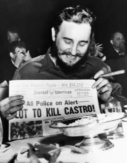 jnaday:     Castro smiles at the headlines of the daily paper.1959.