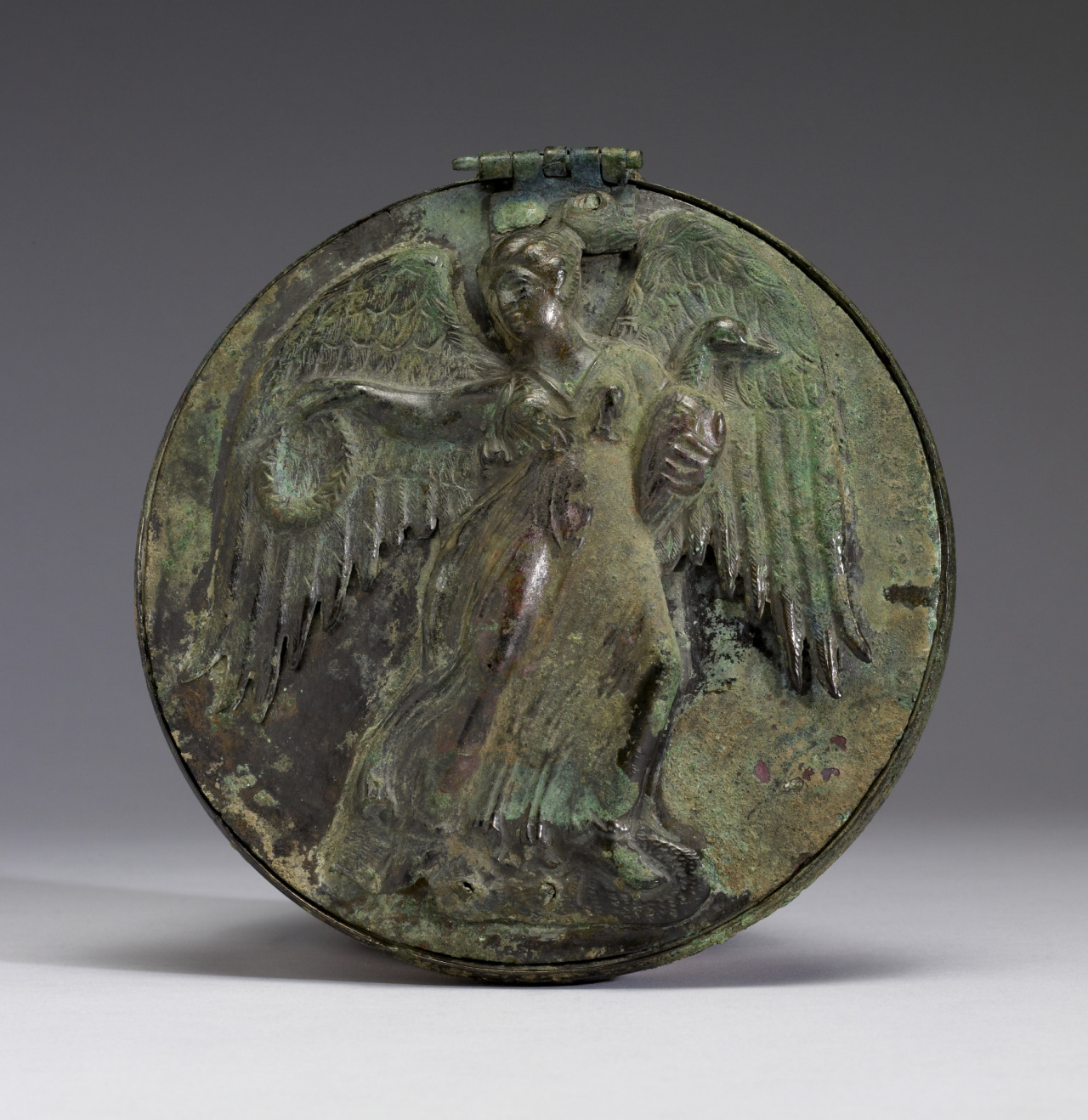 ancientart:  Ancient Greek Mirror with Winged Female Holding Wreath and Goose, 3rd century BC, bronze. Courtesy & currently located at the Walters Art Museum, Baltimore, USA:  A winged woman (possibly Nike, the goddess of victory) rendered frontally in repoussé adorns the cover of this large hinged mirror. She moves swiftly to the right as she glances back over her shoulder. In her left hand, she holds a swan or goose close to her body. Her extended right hand holds a wreath. The loose, flowing garment clings to the figure, revealing her body beneath. Such a mirror would have been a suitable offering to a heroine. In vase-painting Helen is frequently shown holding a mirror, an attribute that emphasizes her celebrated beauty; it also appears in vase-painting as an attribute of brides. The wings of the goddess Nike, who personified military victory as well as triumph in athletic or musical competitions, probably indicate her ability to bring swift victory. She was also associated with love and the world of women.