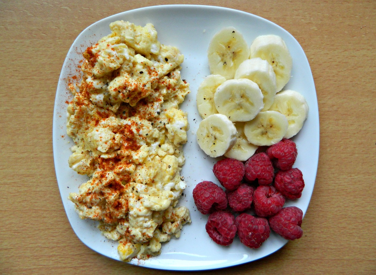 Scrambled eggs with paprika, basil and black pepper, half a banana and a handful of raspberries. (Eggs (yup, cage free, spare eggs from local chickens!) - 2 whole, 1 white, splash of almond milk and sweet chilli sauce, cooked in coconut oil.)