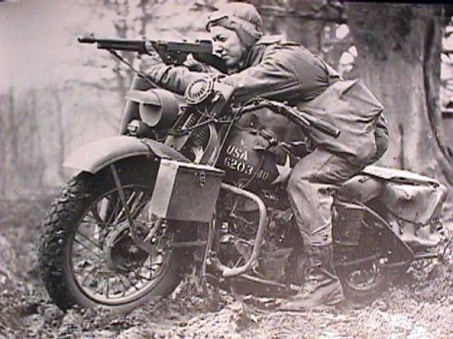 wwii-in-photographs:  A US Army private on a Harley Davidson 'Liberator' shooting with his Thompson gun, uknown location, unknown date.