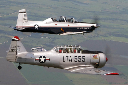"A T-6A Texan II aerial demonstration aircraft flies side-by-side with a vintage T-6 Texan. The two-ship flyby is called a ""Texan Flight."" The T-6A Texan II is flown by Maj. Todd Daggett, team chief and show pilot. The vintage T-6s are flown by a cadre of military aviation enthusiasts. (U.S. Air Force photo) http://www.af.mil/photos/mediagallery.asp?galleryID=23&page=6"