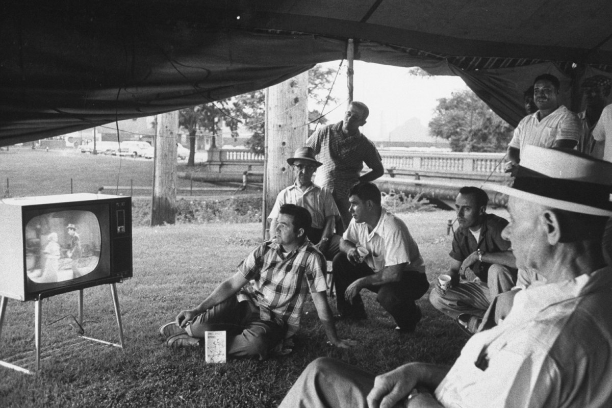 Picketing workers watch TV in a tent outside the gates of a US steel plant during a strike. Gary, Indiana, 1959. By Francis Miller