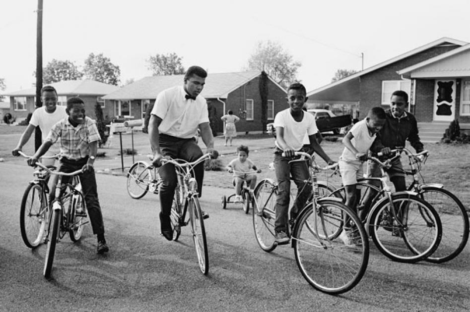 ventureandvirtue:  Muhammad Ali (bicycling with kids), Louisville, KY 1963 Photo by Steve Schapiro