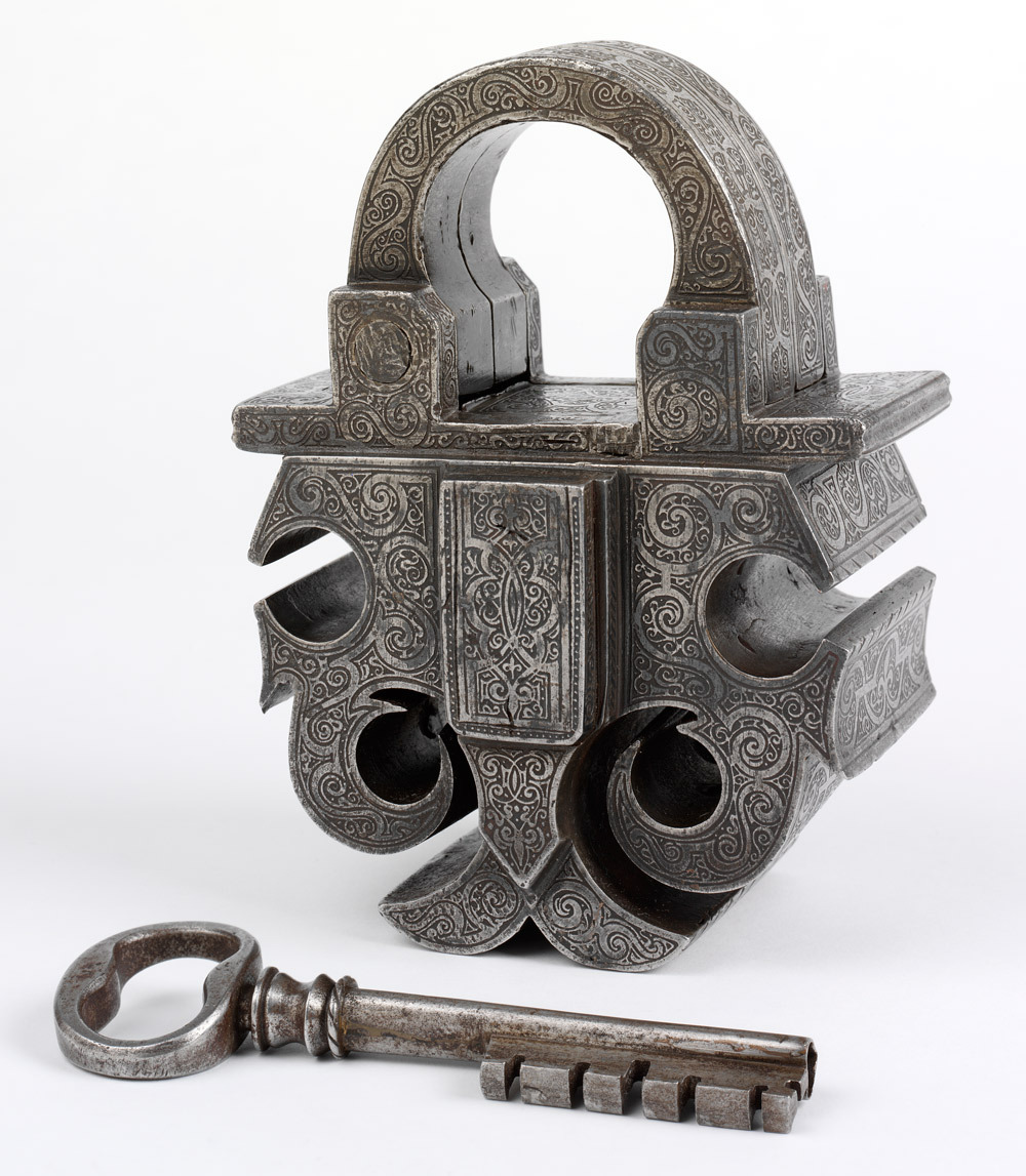 Masterpiece padlock and keySouthern GermanySteelAbout 1580 To become a master locksmith an apprentice had to produce a 'masterpiece'. Here the locksmith demonstrated his skill by creating a robust and secure lock and refining its appearance with delicate etching. Similar patterns decorated other 16th century goods and furnishings, from embroidery to tooled leather. Designs circulated among craftspeople through printed versions on paper and were widely recommended in pattern books.