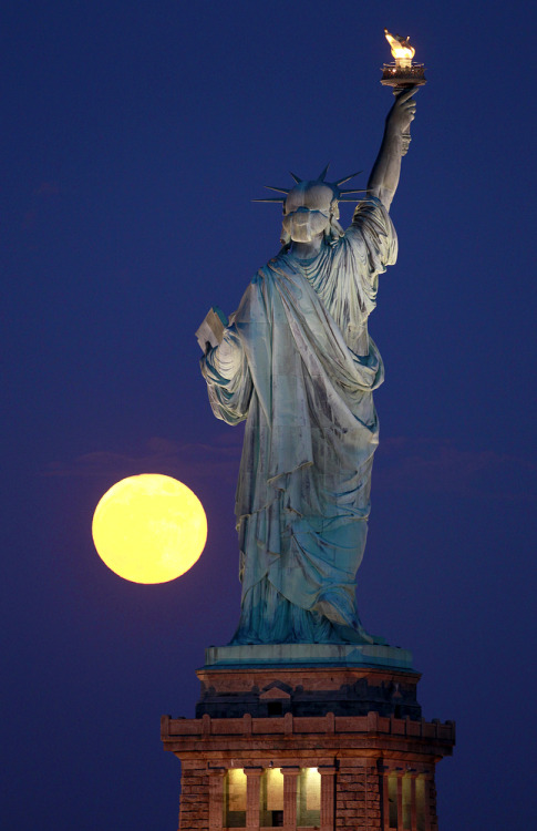 petapeta:  Photos: The 125th Anniversary of the Statue of Liberty - Plog  The moon rises near the Statue of Liberty as seen from Liberty State Park, Wednesday, June 15, 2011 in Jersey City, N.J.