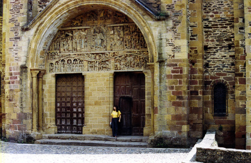 Saint Foy abbey-church in Conques, France @credits  The St. Foy abbey-church in Conques was a popular stop for pilgrims on their way to Santiago de Compostela. There is little exterior ornamentation on Conques except necessary buttresses and cornices. The exception to this is the Last Judgment tympanum located above the western entrance. As pilgrimages became safer and more popular the focus on penance began to wane. Images of doom were used to remind pilgrims of the purpose of their pilgrimage. The tympanum appears to be later than the artwork in the nave. This is to be expected as construction on churches was usually begun in the east and completed in the west. The tympanum depicts Christ in Majesty presiding over the judgment of the souls of the deceased. The cross behind Christ indicates he is both Judge and Savior. Archangel Michael and a demon weigh the souls of the deceased on a scale. The righteous go to Christ's right while the dammed go to Christ's left where they are eaten by a Leviathan and excreted into Hell. The torture of Hell are vividly depicted including poachers being roasted by the very rabbit they poached from the monastery. The tympanum also provides an example of cloister wit. A bishop who governed the area of Conques but was not well liked by the monks of Conques is depicted as being caught in one of the nets of Hell. The virtuous are depicted less colourfully. The Virgin Mary, St. Peter and the pilgrim St. James stand on Christ's left. Above their heads are scrolls depicting the names of the Virtues. Two gable shaped lintels act as the entrance into Heaven. In Heaven Abraham is shown holding close the souls of the righteous A pudgy abbot leads a king, possibly Charlemagne, into heaven. St. Foy is shown on the lower left kneeling in prayer and being touched by the outstretched hand of God. The tympanum was inspired by illuminated manuscripts and would have been fully colored, small traces of the color survive today.