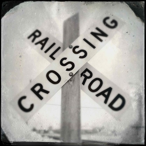 """Rail Road Crossing""  For your daily dose of Hipstamatic this image of a railroad sign.  Sometimes I take pictures and look at them and say does this have any photographic value?  This is one of those images. Hipstamatic 261, Type D film and Tinto 1884 Lens"