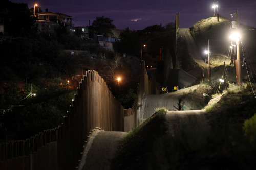The border wall, illuminated at night in Nogales, Arizona, on July 6, 2012. (Sandy Huffaker/Getty Images)  From In Focus's On the Border.