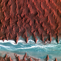 Earth From Space: Dune 45 by europeanspaceagency on Flickr.Via Flickr: Korea's Kompsat-2 satellite captured this image over the sand seas of the Namib Desert on 7 January 2012. The blue and white area is the dry river bed of the Tsauchab. Black dots of vegetation are concentrated close to the river's main route, while salt deposits appear bright white. Running through the river valley, a road connects Sossusvlei to the Sesriem settlement. At the road's 45th kilometre, seen at the lower-central part of the image, a white path shoots off and ends at a circular parking area at the base of a dune. This is Dune 45, a popular tourist stop on the way to and from Sossusvlei. In this image, there appears to be some shadow on the western side. From this we can deduce that the image was acquired during the late morning. ESA supports Kompsat as a Third Party Mission, meaning it uses its ground infrastructure and expertise to acquire, process and distribute data to users.   This image is featured on the Earth from Space video programme. For more information, please click here. Credits: KARI/ESA