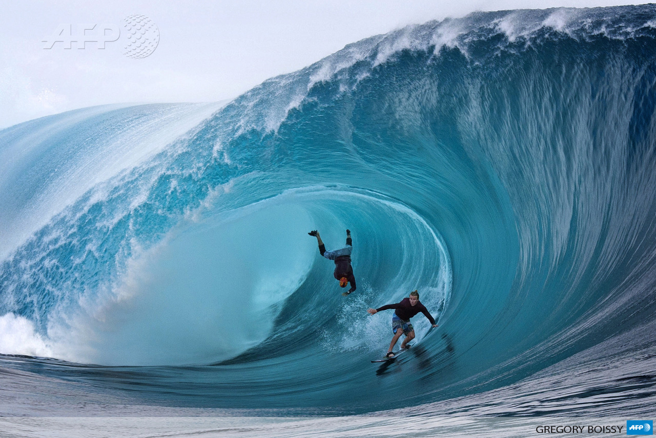 FRENCH POLYNESIA, Teahupoo Reef : US Garrett McNamara (L) and US Mark Healey (R) compete during a free session of surf tow in, in the southern Pacific ocean island of Tahiti, French Polynesia, on June 1, 2013 in Teahupoo. AFP PHOTO GREGORY BOISSY