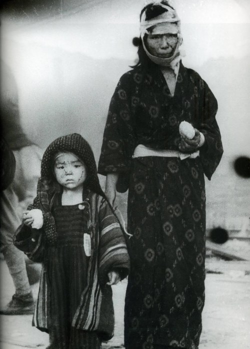A mother and child, survivors of the Nagasaki blast, carry boiled-rice balls that were distributed during emergency relief efforts. photo by Yosuke Yamahata