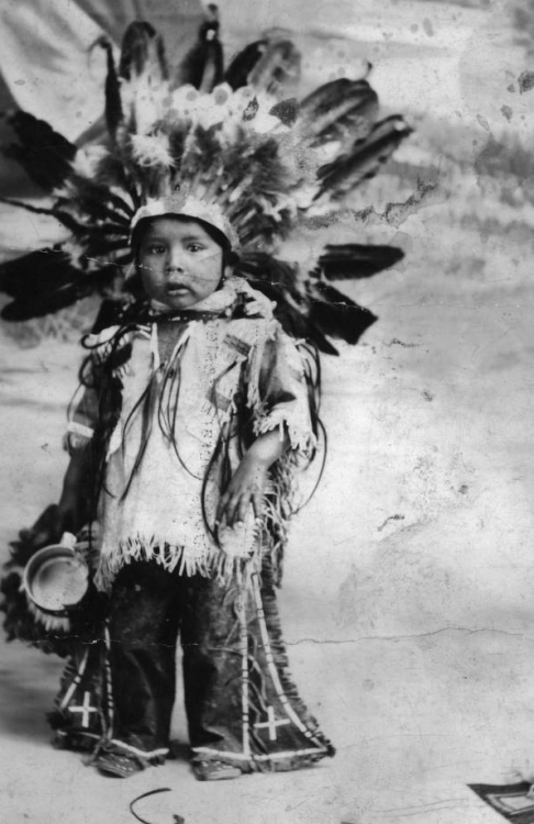 boys-of-the-past:  A Native American (Sioux) boy, identified as Blue Cloud, poses outdoors. He wears moccasins, leggings, a fringed shirt, and a feather headdress. He holds a metal cup - 1880.