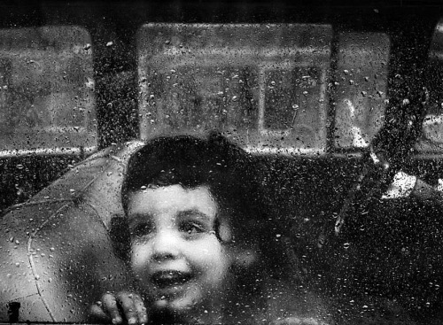 "burnedshoes:  © Mary Frampton, LA Times, 1963, Through the wet window ""You'll find that life is still worthwhile, if you just smile."" ― Charles Chaplin  Los Angeles Times staff photographer Mary Frampton took this 1963 photo of a little girl peering out of a car window during a heavy San Fernando Valley shower. For her efforts, Frampton won best photograph in the suburban sections at the 1964 Los Angeles Times Editorial Awards. (+)"