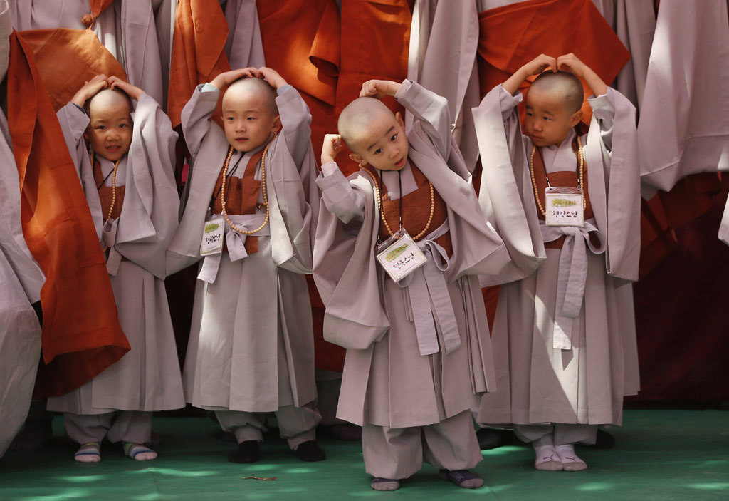 Young Buddhist monks feel their newly shaved heads in Seoul