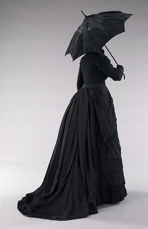 Mourning ensemble, ca 1870 US, the Metropolitan Museum of Art  Black mourning dress reached its peak during the reign of Queen Victoria (1819-1901) of the United Kingdom in the second half of the 19th century. Queen Victoria wore mourning from the death of her husband, Prince Albert (1819-1861), until her own death. With these standards in place, it was considered a social requisite to don black from anywhere between three months to two and a half years while grieving for a loved one or monarch. The stringent social custom existed for all classes and was available at all price points. Those who could not afford the change of dress often altered and dyed their regular garments black. The amount of black to be worn was dictated by several different phases of mourning; full mourning ensembles were solid black while half mourning allowed the wearer to add a small amount of white or purple. Mourning clothing tended to follow the fashionable silhouette of the period, much like this exquisitely finished full mourning dress. This dress shows typical high style 1870s touches such as asymmetry, the bustle back and decorative hem details. The refined details are worked in black crinkled crepe, a common textile used for mourning attire, which indicates that the owner may have had the garment produced for a special occasion.