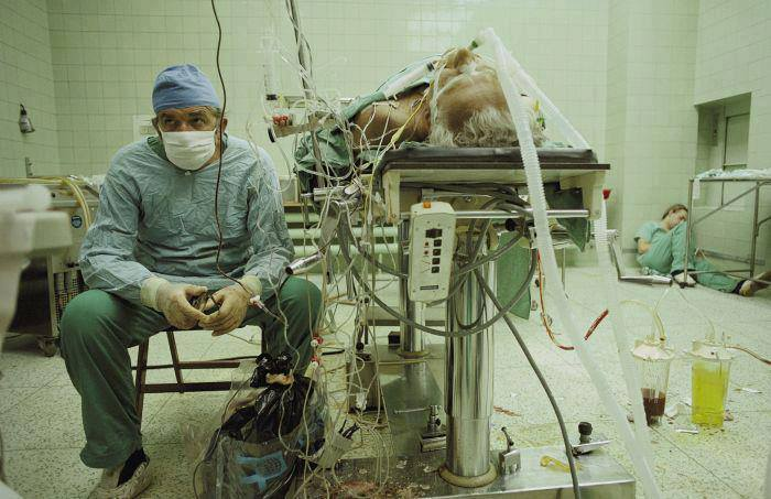 Polish heart surgeon after 23 hours long heart transplantation. Surgery was successful. His assistant is sleeping on the floor (1987)