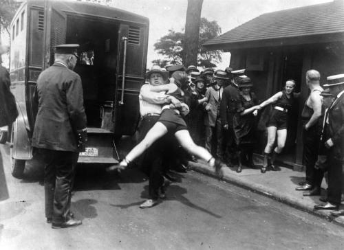historiespast:  Women in Chicago being arrested for wearing one piece bathing suits, without the required leg coverings. 1922