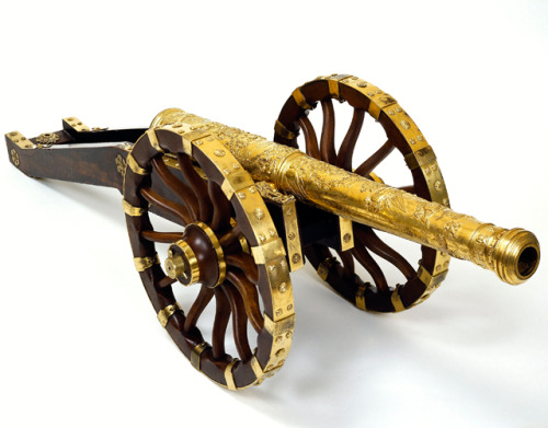 Small artillery model given to the King by the Parliament of Franche-Comté © Paris - Army Museum, Dist. RMN-Grand Palais / Pierre Mérat @credits   This small artillery model was given to Louis XIV by the Parliament of Franche-Comté in 1676. This remarkably well-executed piece depicts an important step in the formation of the territory of France. The attachment to France of Franche-Comté, which until then had been owned by the King of Spain, only became effective in 1678, with the signing of the Nimègue peace treaty, which put an end to the Dutch War (1672-1678). For the dignitaries of Franche-Comté, this gift was a way of showing their attachment to the King.  The cannon is the work of the engraver Laurent Ballard. Made of gilded bronze, it is richly adorned from the breech to the mouth. All the iconography glorifies the Sun King. On the barrel, Louis XIV is depicted dressed as a Roman Emperor, surrounded by laurels (visual 2). At the end of the barrel is a decoration of trophies (drums, armour, weapons) above the coat of arms of the kingdom of France, topped by the royal crown and decorated with the necklaces of the orders of Saint Michael and the Holy Spirit. On the first support, we see depictions of the sieges of Besançon (visual 3) and Dôle, the two main cities of Franche-Comté. On each one, Louis XIV appears as head of the armies, on horseback, with his commanding baton. A lion issant holding a ball is depicted on the breech (visual 4). The carriage, made of fruit tree wood and gilded brass, is decorated with fleurs de lys and royal suns. It fits in with the technical and iconographic richness of this small decorative cannon, a celebration of the King.