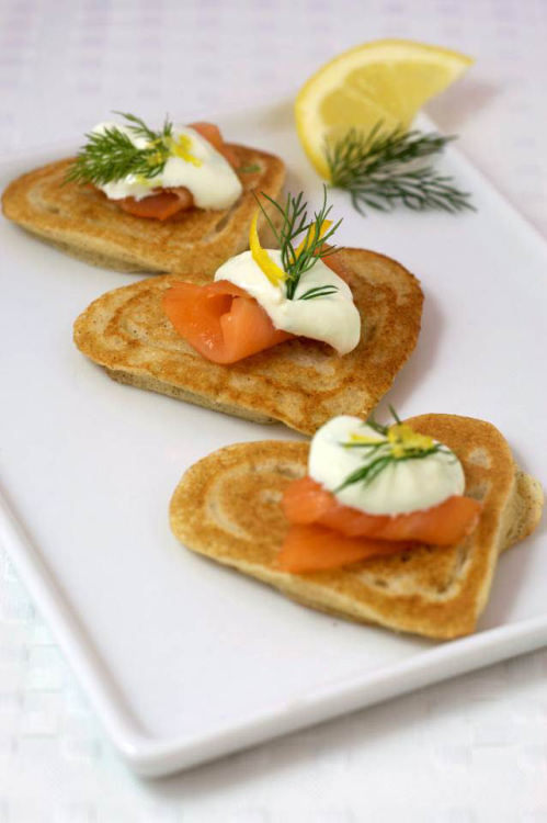 Heart-Shaped Blini with Smoked Salmon and Lemon Caper Sour Cream Makes about 36 heart-shaped blini (3 per serving) Blini Batter Ingredients: 1 tsp. active dry yeast 1/2 tsp. sugar 2 Tbs. warm water (110°F to 115°F) 1 cup warm soy, rice or dairy milk (110°F to 115°F) 1 1/4 cup all-purpose flour 1/2 cup buckwheat flour 1 tsp. salt 1/2 cup Redwood Hill Farm Plain Kefir 2 Tbs. melted butter or Earth Balance Buttery Spread, plus 1/4 cup for cooking 2 large eggs, separated Lemon Caper Sour Cream Ingredients: 1 (12-oz) container Green Valley Organics Sour Cream 1 clove garlic, pressed or finely minced (1 tsp.) 3 Tbs. fresh lemon juice 2 Tbs. fresh lemon zest 2 Tbs. chopped fresh dill, plus more for garnish 2 Tbs. finely chopped red onion 1/4 cup capers, chopped, plus more for garnish Salt and fresh cracked black pepper, to taste 1/2 lb. thinly sliced smoked salmon, cut into 36 bite-size pieces Preparation: 1. Stir together yeast, sugar and water in a large bowl to dissolve. Stir in milk and let stand 5 to 7 minutes, until frothy. 2. Sift flours and salt into a separate bowl. Whisk in yeast mixture, then whisk in Redwood Hill Farm Plain Kefir, melted butter and egg yolks. Cover the bowl tightly with plastic wrap, set in a warm place and allow to rise for one hour. 3. Beat egg whites until soft peaks form. Fold into batter, cover with plastic wrap and allow to rise 30 minutes longer. The batter should be bubbly. 4. While the batter rises, whisk together sour cream, garlic, lemon juice, lemon zest, dill, onion and capers in a small bowl. Adjust seasonings and add salt and pepper to taste. Cover and refrigerate until ready to use. 5. Heat a skillet over medium heat. Place batter in a squeeze bottle using a funnel. Add a tablespoon of melted buttery spread and swirl the pan to coat evenly. 6. Squeeze the batter into the outline of a heart and fill in the heart outline with batter. Cook about 1 to 2 minutes, until bubbles appear, flip and cook 30 seconds longer. 7. Place cooked blini on a parchment-lined baking sheet and keep warm in a 200°F oven until ready to serve. Serve topped with smoked salmon and a dollop of Lemon Caper Sour Cream.