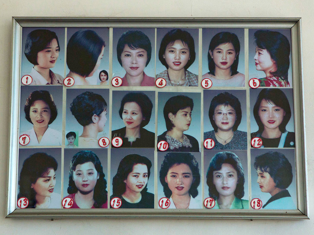 Photos showing example hair styles hang inside a hair salon in Pyongyang, North Korea on Feb. 20, 2013. North Korean women have a choice of 18 officially sanctioned haircuts which have been approved by officials wanting to clamp down on western influences. Likewise, the strict guidelines also apply for men. [Credit : David Guttenfelder/AP]