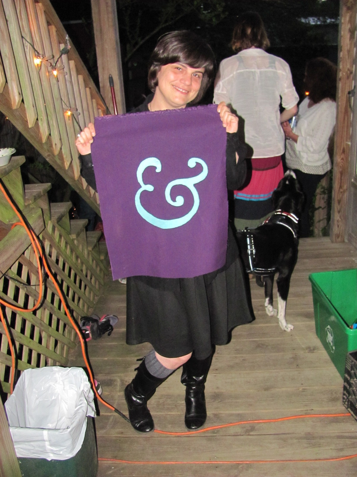 Liz holding the ampersand. Friday, at the GSEX end-of-the-semester party, we presented Dr. Hutchinson, Department Chair, with none other than a purple and teal ampersand GSEX logo screen-printed backpatch in honor of her retirement! After we had cake and other deliciousness, party-goers signed it with sharpies.