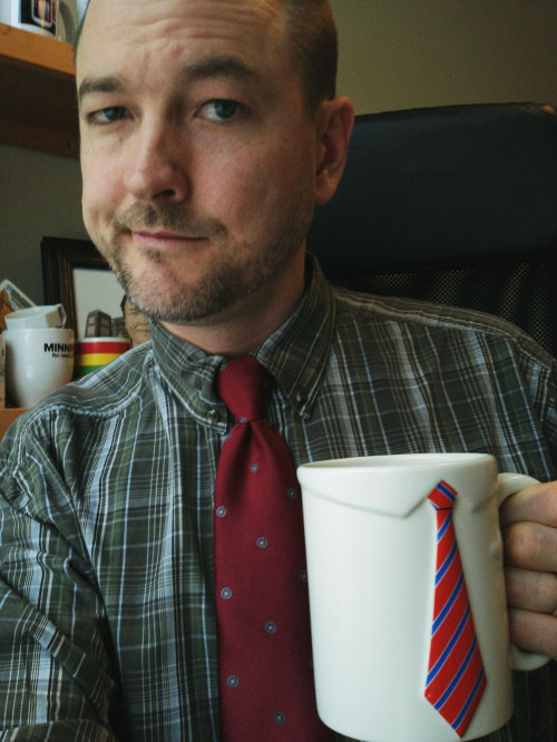 "Mugshot Monday - ""Necktie Coffee Mug by PLUG"" with Birchwood Blend by Peace Coffee I don't wear ties often. And that's pretty obvious. My friend Dave Gatzmer designs really cool coffee mugs for his company PLUG (like this Necktie Coffee Mug and this Donut Coffee Mug, and more.) He gave me this mug and I was dismayed today when I realized my shirt and tie combos are sorely outdated. This was the best I could do. Oy. Gatzmer's coffee mug has inspired me to go find some acceptable shirts and ties for future mugshots. I may even seek out some fashion advice from Chank and Tim Brunelle — they are some very dapper dudes. We'll see how that goes and maybe I'll redo this mugshot."