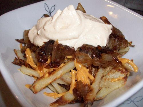 """Animal Style"" Baked Fries Ingredients 2 large russed potatoes, rinsed and peeled Cooking spray 1 tsp. garlic powder 1 1/2 tsp. salt 1/2 medium-sized onion, roughly chopped 1 Tbsp. granulated sugar 1/2 cup vegan sour cream (try Tofutti brand) 1/2 tsp. chili lime seasoning (try Tajin brand, which I found in the fruit aisle at Safeway!) 1/4 cup shredded vegan cheddar cheese (try Daiya brand) Instructions Preheat the oven to 450 F. Cut the potatoes into the shape of French fries, trying to keep them as uniform as possible so that they cook evenly. Place in a microwave-safe dish, cover with water, and cook for 8 minutes in the microwave. Spray a baking sheet with cooking spray. Remove the potatoes from the microwave, drain, and pat dry with a paper towel. Spread eenly on the baking sheet, then spray the tops with more cooking spray. Sprinkle with the garlic powder and 1 teaspoonful of the salt. Bake until brown and crispy, approximately 35 to 45 minutes. Spray a saute pan with cooking spray. Add the onions and sprinkle with the sugar and remaining salt. Cook on low heat until the onions are caramelized and tender, about 15 minutes. Set aside.  In a small bowl, mix the sour cream and chile lime seasoning until well combined.  While the fries are still hot out of the oven, sprinkle with the vegan cheese and top with the caramelized onions and sour cream mixture. Enjoy! Enjoy!"