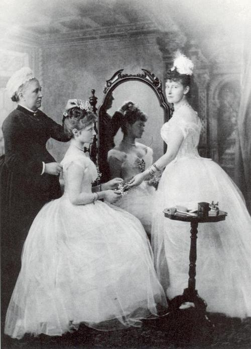 "arkhangelskoye:  Alix of Hesse prepares for her first ball in 1889. Arranging her hair is her English nurse, Mrs. Orchard, while her sister Yelizaveta Feodorovna (""Ella"") supervises."