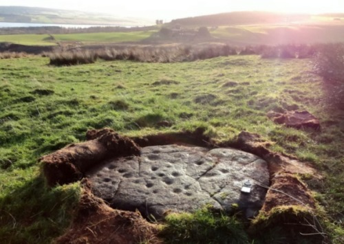 "'Largest' Scottish ancient artworks revealed  A retired silversmith has ­uncovered the largest collection of ancient rock art ever found in the Highlands on a remote hill overlooking the Cromarty Firth. The carved rocks – some ­almost 10ft across – have been discovered scattered across a hillside near Evanton, in ­Ross-shire. Douglas Scott, the amateur archaeologist who has recorded the remarkable find, believes the ""cup-marked"" rocks – dating from up to 5,000 years ago to the Neolithic or Bronze Age – form part of a ""ritual centre of some significance"" where ancient people worshipped the sun and performed rites connected to the ­underworld. Mr Scott, 64, from Tain, has found and recorded a total of 28 carved rocks on Swordale Hill – Druim Mor in Gaelic – and lodged his remarkable discovery with the Highland Historic Environment Record and the Royal Commission on Ancient ­Monuments. He explained yesterday that farmers had first found a small number of the carved stones, with hollow cup-marks carved into them, in 1985. A year later, he and and Bob Gourlay, then the Highland regional archaeologist, scoured Swordale Hill and recorded and photographed ­another 14 cup-marked rocks on the ridge. Mr Gourlay has since died and over the past two years, Mr Scott, has completed the task of searching the entire hilltop and has now photographed and ­recorded 28 carved rocks across the site. He said: ""The finding of up to 28 cup-marked rocks on Druim Mor makes this the largest concentration of cup-marked stones so far found in the north of Scotland. Cup-marked stones are not unique but this is the biggest concentration found in this area and that is quite significant in itself because no-one knew these monuments were up there."" Mr Scott added: ""The carvings on the rocks are anywhere between 4,000 and 5,000 years old and comprise hollows, some surrounded by rings, and grooves which all line up to where the sun rises in midwinter. There is a concentration of them, spread across 150 metres."" There is also a chambered burial cairn and a circular ditch, possible evidence of an ancient henge, on the hill. Mr Scott added: ""From the ridge, there are wide views across the fertile lands of the Cromarty Firth, the Black Isle and the distant Cairngorms. According to Gaelic folklore, these ancient people believed that the sun was rising and setting in the underworld. ""They would carve these cup marks into the rock at the times when the sun was coming up, out of what they believed was the underworld."" He said cup marks can be found throughout Europe, where they are associated with carvings of the sun, solar ­chariots and boats – the latter believed to carry souls of the dead to the underworld. Mr Scott said: ""The position of the cup marks, between the passage cairn and the henge, suggests that this was one of the most important ritual sites in the area."""