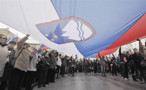 "The uprising in Slovenia: Europe's latest popular challenge to austerity & corruptionFebruary 20, 2013 During the crisis in Europe we've seen democracy harmed by the power of financial markets. Take Greece and Italy, where investors essentially decided who would become those countries' banker-prime ministers without so much as consulting the citizenry. In this kind of anti-democratic climate, protesters despite their growing numbers remained unheard. This time, though, as mass demonstrations grow into the tens of thousands in recent weeks, people in Slovenia have a chance to make a difference. This small country of 2 million, lodged in the middle of Europe, belonged to Yugoslavia until 1989 though today it is more similar economically to its northern neighbor Austria than to other post-Yugoslav republics. Slovenians joined the European Union in 2004 and the Euro-zone in 2007. With an export-oriented economy that has done quite well, Slovenia became something of an example for other countries to follow. It inherited certain social characteristics from the former Yugoslavia, which enabled it to share common goods relatively equally and keep the income gap small; meanwhile, its solidly democratic foundations provided wide legislative representation. But the dark days arrived here too after September 15, 2008 and the bankruptcy of Lehman Brothers. Slovenia's export-driven economy couldn't protect itself against the recession that hit other European countries, and many companies went bankrupt. According to the National Bank of Slovenia, the percentage of all unpaid credits as a result of companies which sank and failed to pay back loans is 13 percent; other economists say the number could be as high as 25 percent. In short, Slovenia may soon be the next EU member in need of a bailout. This comes at a time when the situation for ordinary people is worsening as the unemployment rate has climbed to 12.2 percent. Meanwhile, a political impasse over the last year enabled Janez Janša and his right-wing Slovenian Democratic Party to form a government that subsequently started to decrease public spending. Social programs that help the unemployed, students and retirees have started, like elsewhere, to be cut. Under the growing pressure of austerity, vocal groups of protestors are now appearing in the streets—most recently, from an unexpected turn of events. Last October, Franc Kangler, the mayor of Maribor, Slovenia's second largest city, decided to build a speed camera system throughout the city and its neighborhoods. Speed traps were imposed by a private-public partnership, and within the first few days the system detected 25,000 traffic offenses. People were outraged—even more so when they discovered that only 8% of the fines were transferred to the city budget. The rest, 92 percent, went to the private company. The Commission for the Prevention of Corruption, an independent state body, accused Kangler of violating the law and began an investigation into the speed camera contract. Meanwhile, 10 of the city's 30 speed traps were physically destroyed during protests—the biggest of which took place on Dec. 3, when 20,000 people amassed and demanded Kangler's resignation. Three days later, amid ongoing protests and unyielding accusations of corruption, Kangler stepped down as mayor. But that was only a beginning. Since then, allegations of corruption have been leveled against Slovenia's Prime Minister, Janez Janša, and against Zoran Janković, the mayor of the capital Ljubljana and leader of the biggest opposition party, Positive Slovenia. On Jan. 8, the Commission for the Prevention of Corruption affirmed that Janković and Janša ""systematically and repeatedly violated the law."" Prime Minister Janša, who was already on trial for corruption, is now being forced to report how he earned—and why he did not previously report earning—more then 200,000 euros in income. For his part, Mayor Janković is in the position of explaining why companies that cooperated with the city of Ljubljana also transferred money into his private account. The success of the demonstrations in Maribor has encouraged Slovenians nationwide now to enter into the streets in protests that are loud and growing louder. ""People simply can't stand having corrupted politicians using people's hard earned money for their own corrupted interests any more,"" said one Slovenian woman protester. The impacts of increased austerity policies are fanning the fire, and protests continued over the past month with Slovenians demanding the resignations of both Janša and Janković. On Jan. 8, 8,000 people turned out to march in Ljubljana. Then, last Friday, Feb. 8, some 20,000 demonstrators filled the streets of the capital, which has about 280,000 residents. Due to the wave of protests, the governing coalition has lost its majority in parliament. Zoran Janković has stepped down as his party's leader, though he remains the mayor of Ljubljana. Meanwhile, all signs point to early Slovenian elections. What is happening right now in Slovenia is extraordinary: people are exercising their power in the streets to peacefully shift authority away from corrupt elected officials. Some have called the movement an uprising. The real challenge, however, and the bigger question still to be answered, is how to rebuild a political and economic landscape after the hurricane sweeps through. Source"