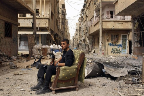 inothernews:  DEAD CALM  A member of the Free Syrian Army holds his weapon as he sits on a sofa in the middle of a street in Deir al-Zor on April 2.  March was the deadliest month during the conflict, with more than 6,000 dead — a third of them civilians.  A British group believes the death toll in the two-year-old war has reached more than 120,000.  (Photo: Reuters via NBC News)