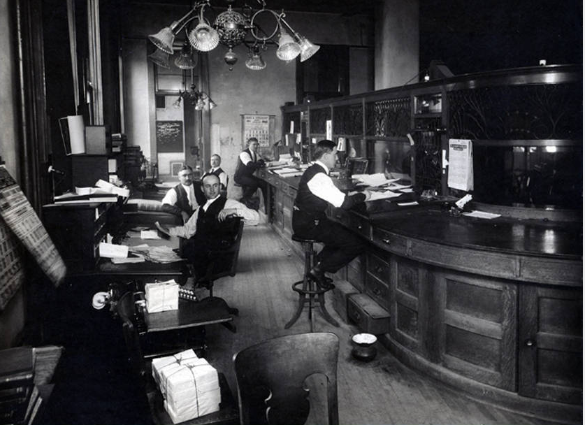 "The city clerk's office is still located in City Hall but looks a bit different from this 1915 picture. Nearly everything in the room would be an antique hunter's delight now - from the lighting fixture to the strategically placed spittoon. Peter F. Leuch was city clerk then - the 20th to hold the position in the city's history - and in 1916 ""manual of the Common Council and of the municipal government"" complied under his direction, a good profile of the city was drawn. It included the usual biographies, also information on the schools offering ""penny lunches"" and a list of license rates. The rates ranged from $10 annually for a double bowling alley ($5 for a single); $5 for ""circuses, dog or pony shows'; $200 for a retail liquor license; $50 for a tally-ho or Columbian horses, $5 for, ""carriage, drawn by 2 horses"" and the same amount for an automobile for hire. (Photo courtesy of Theresa Stoecker and information from the Milwaukee Public Library local history collection.) Date: 1915 Source: Remember When… Milwaukee Public Library Digital Collections"