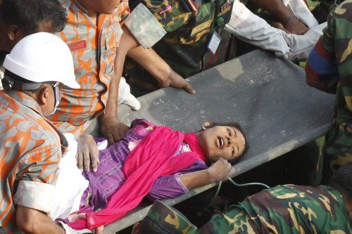 Rescuers pull a woman, identified by Bangladeshi media as Reshma, 17 days after a garment factory collapse that has killed more than 1,000 people.  [Photo: STRDEL/AFP/Getty]