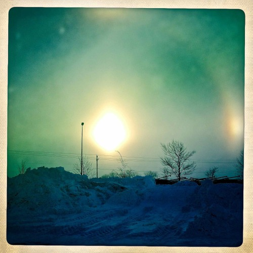 """SUN DOGS""   For you daily dose of Hipstamaic this image of a Sun Dog.  The camera lens was not big enough to capture the full halo.  Without going into the scientific mumbo jumbo if you see a Sun Dog it's going to be a very cold night. -26 below tonight in Fargo, North Dakota. Hipstamatic 261 with John S lens and Ina's 1969 film"