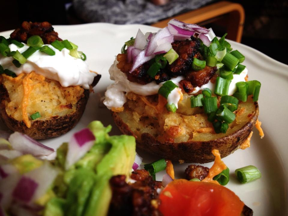 Potato skins with Daiya vegan cheese, Tofutti sour cream, tempeh bacon, green onions, red onions, avocado, and tomatoes!