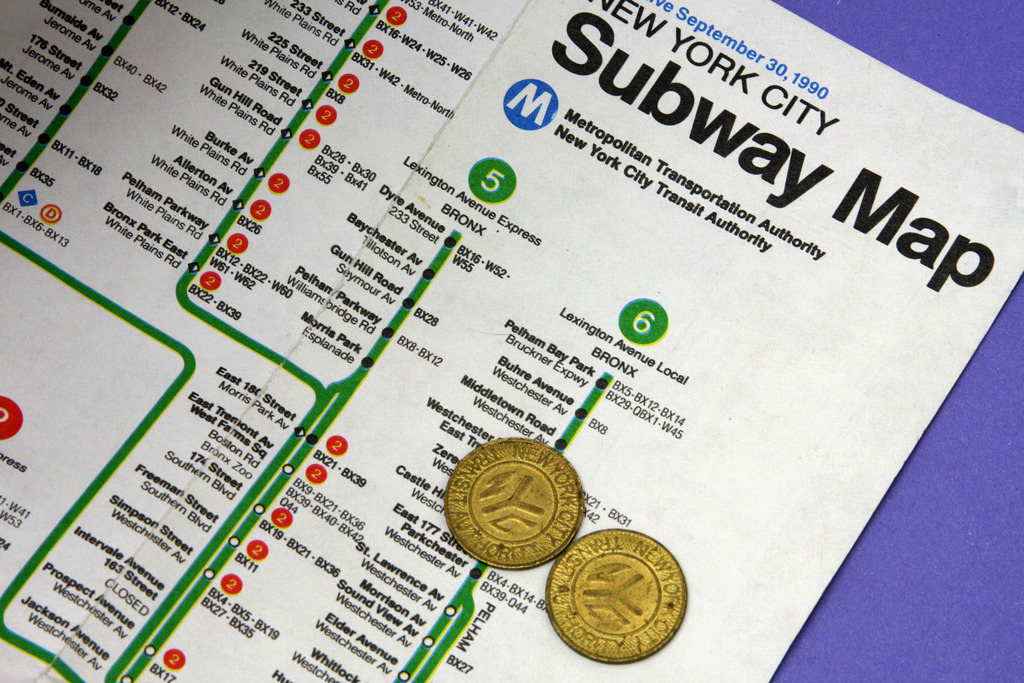 "NY Subway Map and Tokens, 1990 Great little slice of history here. The photographer on Flickr seems to recall the cost of a token as being 60 cents at the time; Wikipedia prices it at $1.15. As a graphic designer, all I can see is the terrible registration in the (cheap) printing — look at the huge yellow halo bleeding out to the right of the green and red printed areas. (In four-colour printing, green is made from combining cyan and yellow inks, red is made from magenta and yellow. When the plates are poorly aligned with each other, the presses run too fast, or cheap paper stretches or moves during the printing process, you get misalignment of the inks, leading to poor registration like this.) EDIT: As has been pointed out to me, the tokens and the map shown in the photo aren't contemporaneous. The ""solid brass"" token shown here was used from 1980 to 1985; during that time, the cost of a subway ride rose from 60 cents to 90 cents. (Source: nycsubway.org's comprehensive page on subway tokens) (Source: jonwa60/Flickr)"