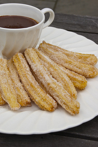 prettygirlfood:  Churros and Chocolate 2/3 c. water2/3 c. flour2 tsp. sugarpinch salt2 tsp. vegetable oiloil for deep fryingcinnamon sugar for dredging (1/3 c. sugar + 1 tsp. cinnamon) Directions Combine water, oil, salt, and sugar in a saucepan and bring to a boil. Add the flour all at once, and combine into a thick paste, pressing with a rubber spatula to break up any lumps of flour. Allow to cool in the pan. Put dough into a canvas pastry bag or cookie press fitted with a large star tip (the dough is very stiff and is hard to extrude with a pastry bag). Extrude out roughly 5 inch long pieces into 375°F oil, 4 or 5 at a time, and cook until golden brown, about 3 or 4 minutes. Drain on paper towels, then toss in cinnamon sugar and serve warm. This will make about a dozen. I served these with a thickened hot chocolate made from 1/2 c. of milk, one disc of Ibarra Mexican-style chocolate, and a 1/2 tsp. of corn starch. Word to the wise: I had a little bit of dough left in the pastry bag that I couldn't extrude out, so I rolled it between my hands to drop in the oil. Don't do this. The exterior of this bit set, then the interior expanded and burst, spraying hot fry oil. I escaped serious injury, but it was a close call.
