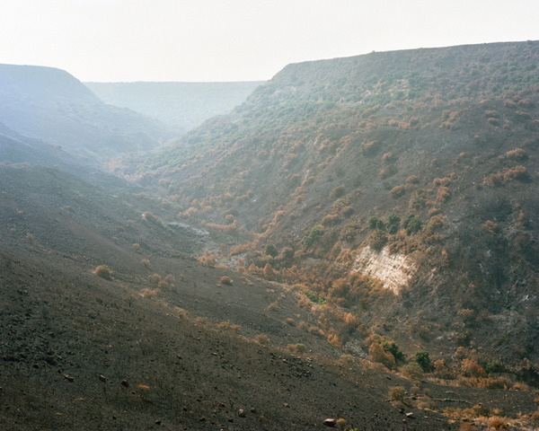 Fire-Ravaged Valley, Gamla, Israel, 2010 by Beth Gilbert (from the series Scarred Land) Beth Gilbert's images from the series Scarred Land build on a foundation of traditional landscape depiction. The sequence of photographs, carefully edited and framed, influences the knowledge we glean from looking. Historic references express the cyclical and perpetual nature of human devastation and its concurrent impact on the earth: here the gorged land, receding away with mountains that frame its destruction, recalls Roger Fenton's Crimea and his photograph Valley of the Shadow of Death. Fenton's photograph sports cannonballs that were strategically placed to create impact; Beth's image substitutes the ravages of fire. Both were made with a documentary impulse to record the impact of war but 155 years separates them and their audience's reactions. Presented to a western audience today, Gilbert's images function as most photographs of distant points do, providing information that constructs an understanding of a place most viewers have never visited. The vegetation growing from the hills undermines the obvious references to war, however, and raises questions. Is this destruction or regrowth? Are we falling or rising? The image refuses to answer, caught between ruined and re-grown, historic and contemporary. Beth A. Gilbert holds a BA from Simmons College and will be pursuing an MFA in photography at the Rochester Institute of Technology beginning in the fall of 2013. Her photographs have been shown at the Danforth Museum of Art, the Boston Online Biennial, and the Hadassah Gallery in Jerusalem, Israel. Currently living and working in Boston, MA, she is a core member of C.R.I.T., a Boston area photography collective.  for more, please visit www.bethgilbert.net