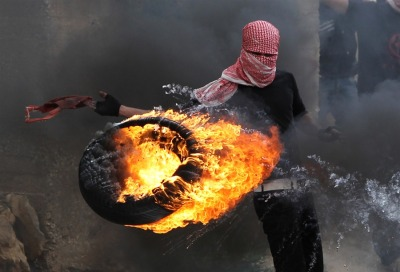 "politics-war:  A Palestinian sets fire to a tire during clashes between hundreds of Palestinians and Israeli soldiers outside the Ofer prison after a march marking the 65th Nakba day or ""Day of Catastrophe"" on May 15, in Betunia near the West Bank city of Ramallah."